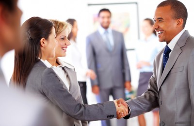 Profile of smiling business people, handshake at the office.