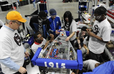 100305-N-7676W-182 WASHINGTON (March 5, 2010) Cmdr. Jim Grove, from the Office of Naval Research Navy Reserve Program 38, left, helps tudents from McKinley Technology High School make adjustments to their robot during the For Inspiration and Recognition of Science and Technology regional Washington, D.C. competition. The team, coached by Grove, is sponsored by the Office of Naval Research. (U.S. Navy photo by John F. Williams/Released)